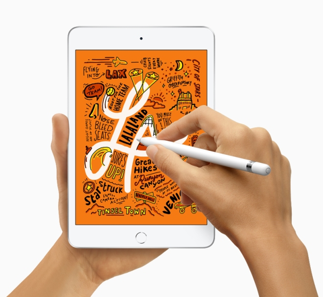 The iPad Mini being held in one hand while the other hand is drawing some text on the screen with an Apple Pencil.