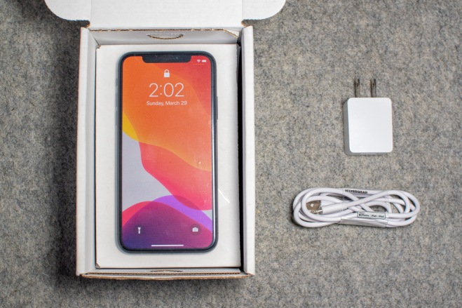 iPhone X in a box next to a charger and lightning cable