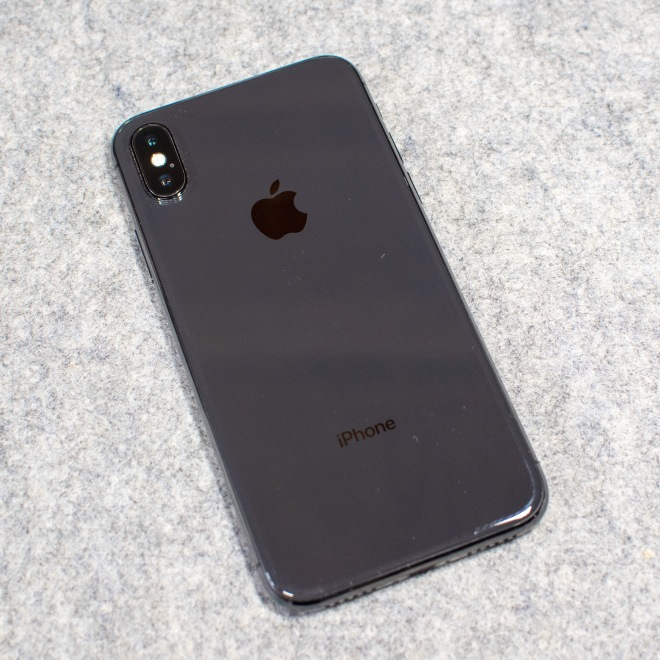 Refurbished iPhone X, face down, on a gray table top