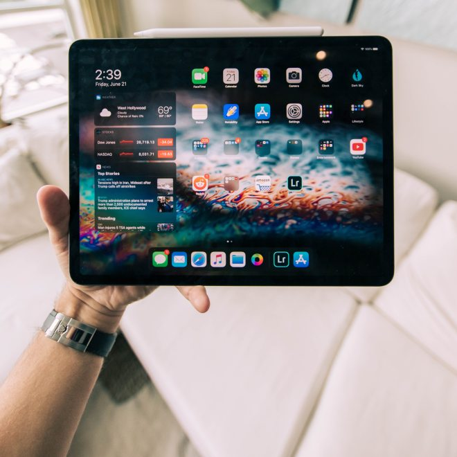 An iPad Pro, with Pencil, being held by one hand above a sofa.
