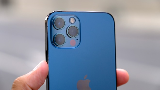 A hand holding a blue iPhone. The back of the phone is facing the viewer.