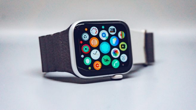 An Apple Watch sitting on a table surface. The screen is on showing the app launcher.