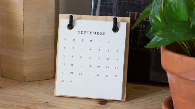 A calendar sitting on a shelf displaying the month of September